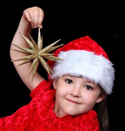schattig meisje in kerst outfit spelen met gouden ster ornament. geïsoleerd op zwart