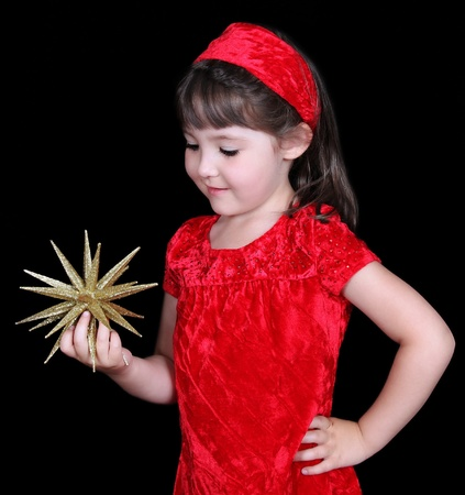 admiring: pretty girl in christmas dress holding gold star. isolated on black