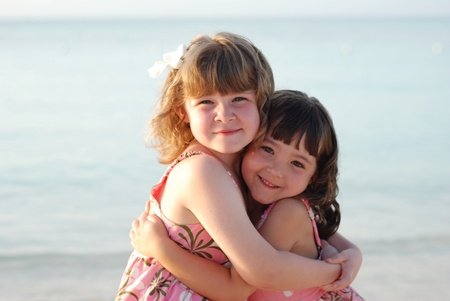 royalty free: twin girls embracing on a warm tropical beach Stock Photo