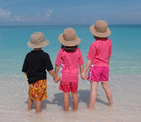 Geschwister stehen in warmen tropischen Wasser am Strand Händchen haltend
