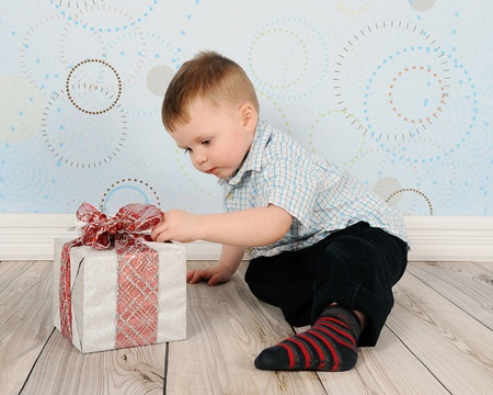 adorable toddler curious about a christmas present in front of him photo