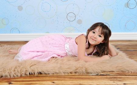 rug: sweet little girl posing on furry brown rug