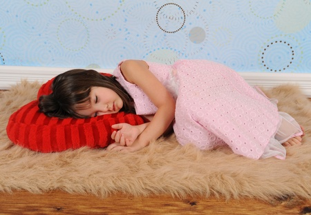 sweet little girl asleep on heart shaped valentine's pillow