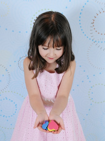 sweet little girl admiring heart shapes she is holding in her hands photo