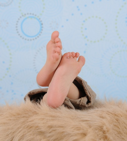 touching toes: close-up of childs feet over a furry blanket
