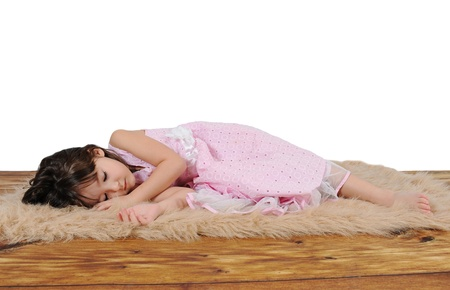 adorable little girl in dress asleep on furry brown rug. over white 免版税图像