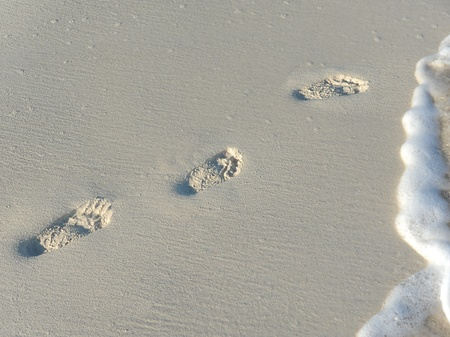 footprints in the sand on a warm tropical beach with the waves rolling in photo