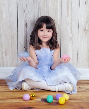 niedliche kleine Mädchen sitzt mit Ostereiern in die Hände