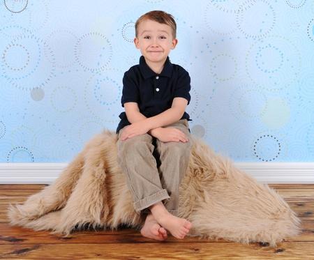 lieve jongen poseren met een dwaze grijns in de studio Stockfoto