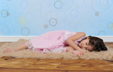 adorable little girl in dress asleep on furry brown rug photo