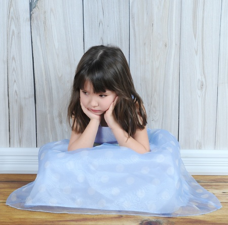 upset little sitting girl with hands on face