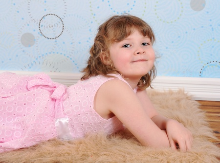 cute little girl  in dress laying on a furry brown rug smiling  photo