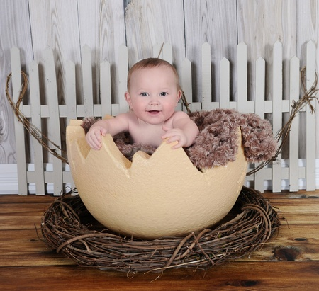 royalty free: happy baby sitting in giant egg prop