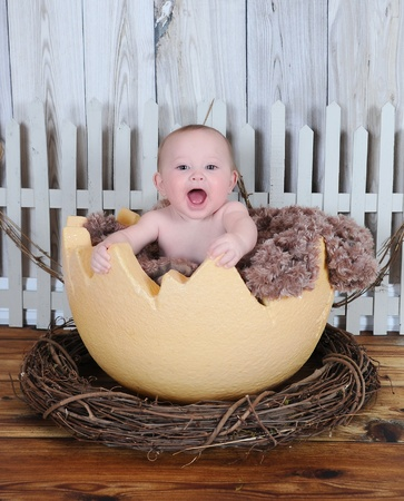 squealing: sweet baby happily sitting in giant egg