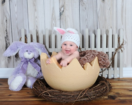adorable baby sitting in giant easter egg with hat and bunny photo