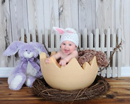 hands free: adorable beb� sentado en el gigante de huevos de pascua con el sombrero y el conejo Foto de archivo