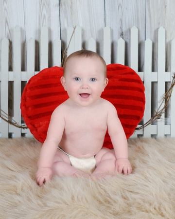 sweet baby boy sitting with large red heart on a furry brown blanket photo
