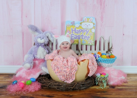 happy baby girl sitting in easter egg surrounded by easter decorations photo