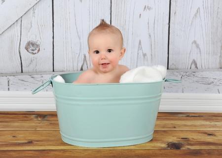 happy baby boy sitting in washtub Stock Photo
