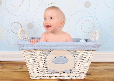 adorable baby boy in blue wicker basket  版權商用圖片