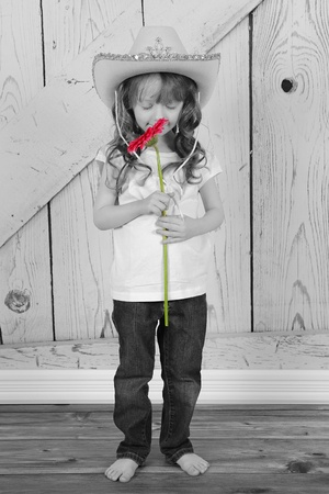 royalty free: adorable cowgirl smelling flower in selective color