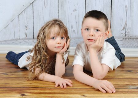 young brother and sister laying together in floor with hands on chin photo