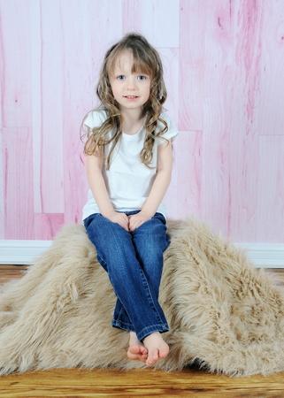schattig klein meisje die zich voordeed op bruin bont tapijt met een roze achtergrond
