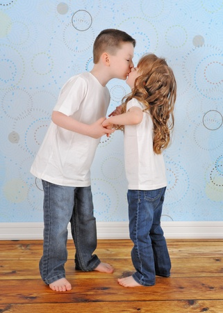sweet young brother and sister sharing a kiss photo