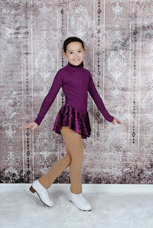 figure skater: beautiful image of young figure skater posing in purple dress