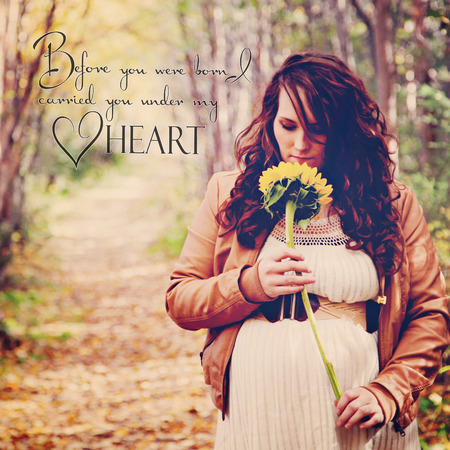 stunning pregnant woman on forest path with quote Stock Photo