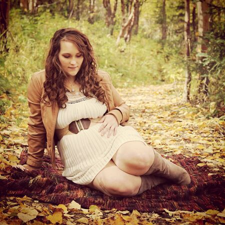 provoking: beautiful of pregnant woman sitting on forest path in fall Stock Photo