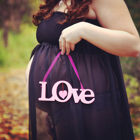 provoking: beautiful of pregnant woman holding quote forest path in fall