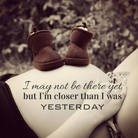 image of booties on pregnant belly with effect and quote