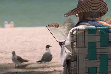 Elderly woman enjoying book at beach