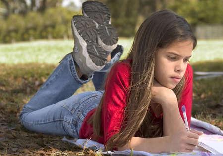 girl doing homework outside Banco de Imagens