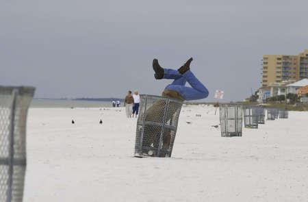 man in trash can at beach