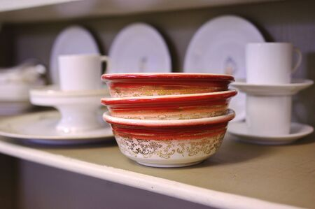 Stack of Vintage Bowls on a shelf amongst an assortment of white dishware in the background. photo
