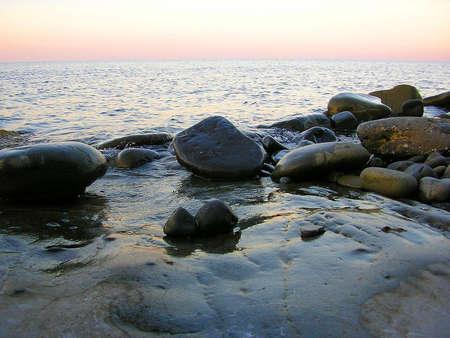 water s edge: Pietre bagnate su una spiaggia vicino al mare blu