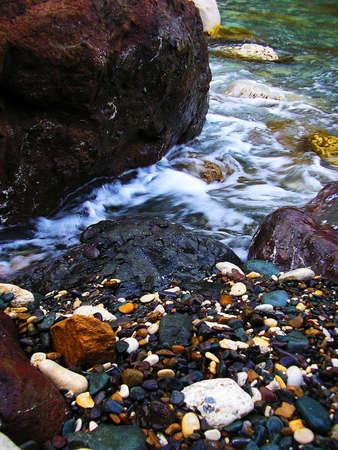 water s edge: Pietre bagnate Multi-colorati su una spiaggia vicino al mare blu
