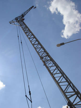 Abstract Industrial background with construction crane on blue sky. Construction site art. Crane and building working progress. Empty Space for text. Construction concept. New buildings with a crane.