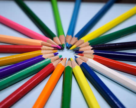 Closeup colorful pencil on blue paper background. Macro of a group pencils in a circle. Business concept, teamwork, united group Zdjęcie Seryjne