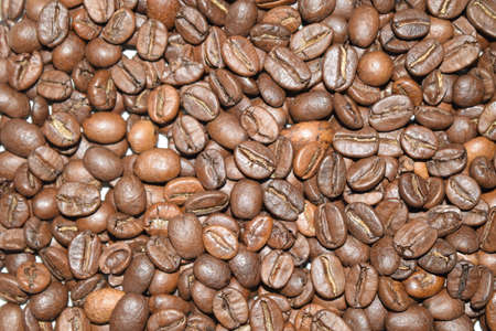 Roasted coffee beans, coffee, aromatic food and drinks. Top view flat texture. Close Up Background. All space filled with coffee beans. Selective depth of field