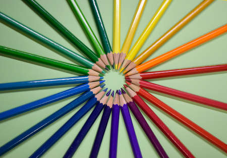 Closeup colorful pencil on green paper background. Macro of a group pencils folded in rainbow colors in a circle. Business concept, teamwork, united group