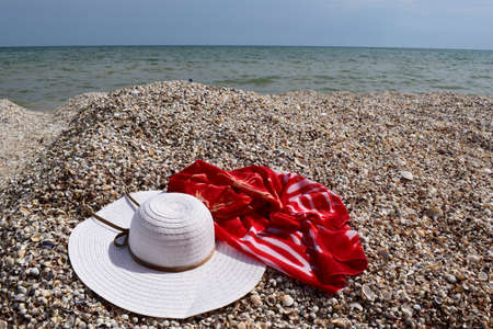 Vintage summer straw beach hat and pareo on the seashore. Accessories for relaxing on the beach. Summer lifestyle. Vacation mood. Reklamní fotografie