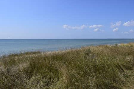 The precipitous shore of the sea in the steppe. Grass landscape near seascape close to sea edge. Beautiful sea landscape. Travel background.