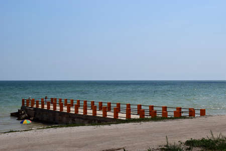 Sea piercing with a pier equipped with wooden railings. Blue sky and sea Stock Photo