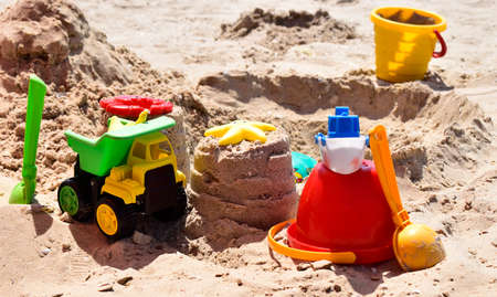 Children's plastic toys green end yellow car, shovel, yellow and red buckets, green ball with yellow sand on the beach by sea. Children's beach toys on sand on a sunny day. Sandbox on the playground Stock Photo - 128108817