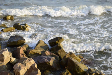 Sea surf, the blue wave hits the rocks. Coastline foam from breaking on the rocks of the sea surf. Wet stones and waves. Background of sea stones and the sea serf for design. Stock Photo