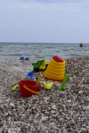 Child's bucket, spade and other toys on tropical beach against sea and blue sky. Plastic children's toys for sand on the background of the sea. Plastic children toys on the sand beach Zdjęcie Seryjne - 129146647