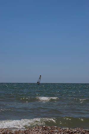 Windsurfing, sailing on the sea in sunny day in summer. 免版税图像